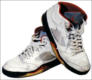 Air Jordan 5, front and side view, white with black, red, and yellow accents