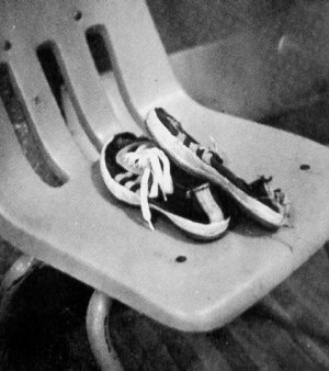 Well-worn pair of Converse Track Training Shoes in a plastic chair
