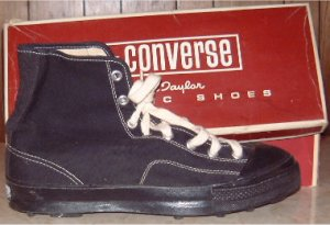 "Side view of black high-top Converse ""Chuck Taylor"" football shoes: outside along with a partial view of the box top"